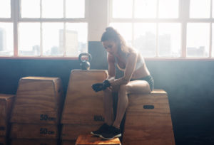 Portrait of tired looking fitness woman sitting on box at gym. She is relaxing after her intense workout.